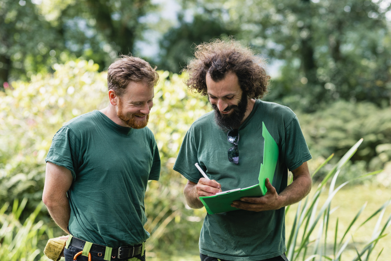 Two landscape gardeners making notes on clipboard